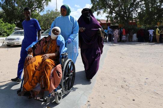 A paramedic and civilians at Madina hospital assist an injured woman after a minibus struck a roadside bomb at Hawa Abdi village, northwest of Mogadishu