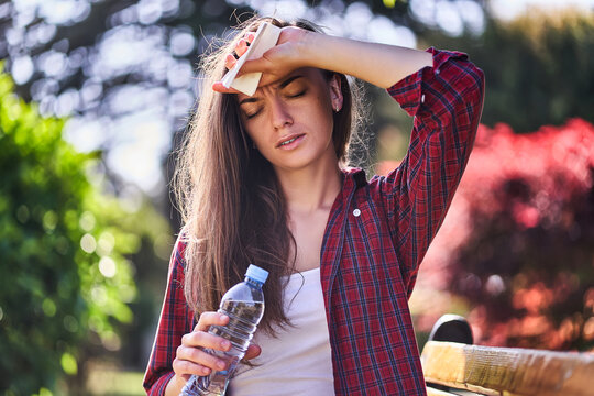 Tired sweating woman with refreshing water bottle hold on to forehead outdoors in hot summer weather