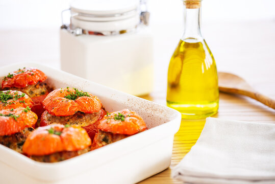 Mediterranean stuffed tomatoes with meat, bread crumbs, and herbs in a white oven dish, aside a bottle of olive oil, a white jar and a serving spoon, all on an oak wood table.