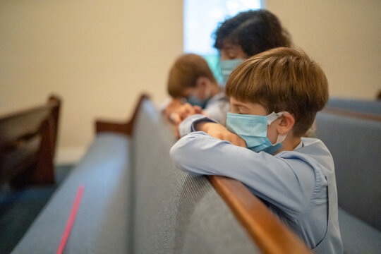 Family praying in church together with mask on.