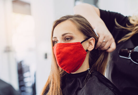 Woman wearing red face mask getting fresh styling at a hairdresser