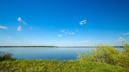 Fototapete - Summer landscape with lake, blue sky and clouds. Nature wilderness. Countryside outdoors, relaxation, space scenic. Beautiful pond, forest, green meadow with reflection in water.
