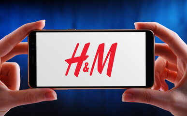 Hands holding smartphone displaying logo of Hennes & Mauritz