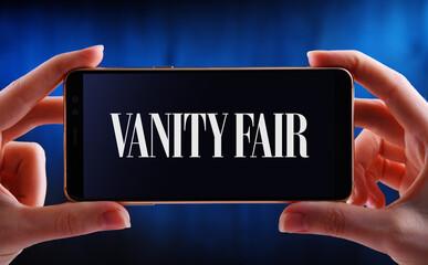 Hands holding smartphone displaying logo of Vanity Fair
