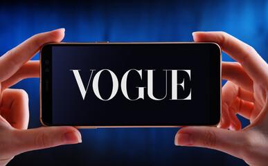 Hands holding smartphone displaying logo of Vogue