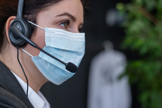Close-up of a woman in a medical mask talking on a headset in an office. Portrait of a female call center operator during a virus outbreak. Business worker answer customer calls during outbreak covid.