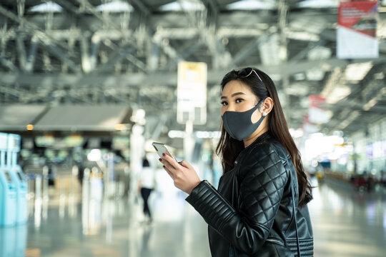 Asian woman traveler wearing face mask walking in airport terminal.