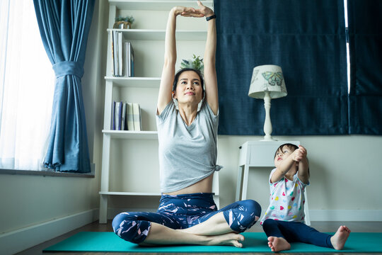 Asian woman exercise yoga, work out at home with children play around