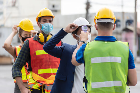 Workers with protective mask, Engineer worker waring surgical mask checking body temperature using infrared digital thermometer check temperature before into work place,