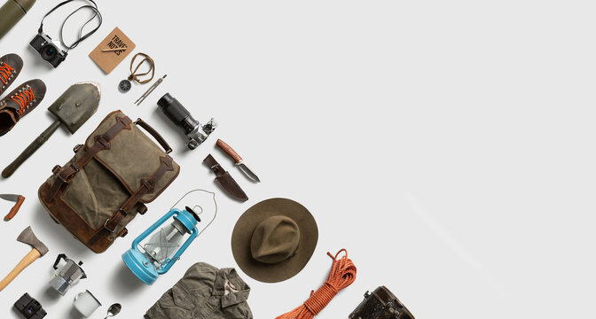 Top view of hiking and camping items arranged on abstract white background with empty space