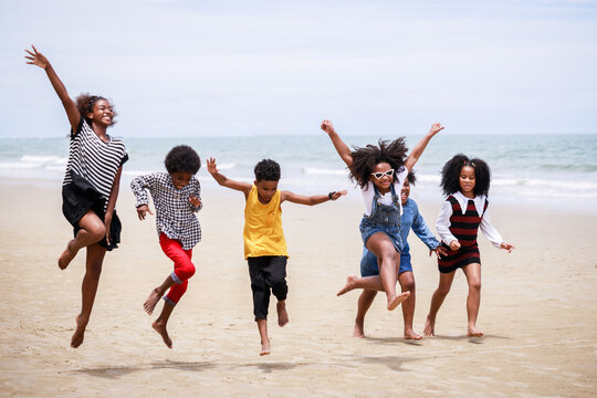 Funny vacation. Children or kids playing and romp together at the beach on holiday. Having fun after unlocking down the city from COVID19. Seven African American kids. Ethnically diverse concept
