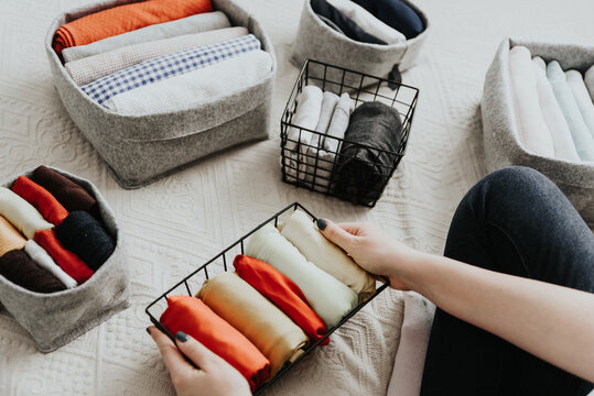 Woman organizing clothes in wardrobe, putting laundry in boxes and baskets. Concept of minimalism lifestyle and japanese t-shirt folding system. Tidy up wardrobe