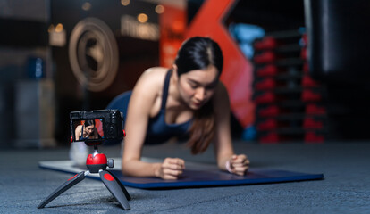 The camera on the tripod is taking pictures or videos. Asian Women Trainer In Good Shape Teaching or performing a sample of plank poses is a bodyweight exercise in online training concept.