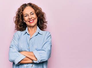 Middle age beautiful woman wearing casual denim shirt standing over pink background happy face...