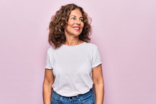 Middle age beautiful woman wearing casual t-shirt standing over isolated pink background looking to side, relax profile pose with natural face and confident smile.