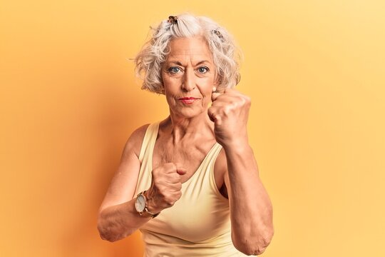 Senior grey-haired woman wearing casual clothes ready to fight with fist defense gesture, angry and upset face, afraid of problem