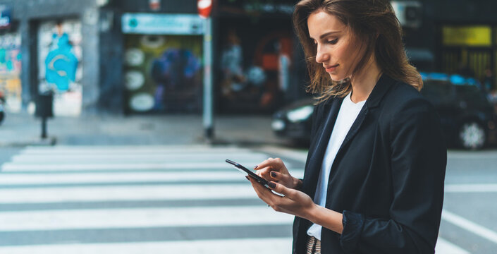 Close-up female hands holding smart phone screen on background of street crosswalk. Young businesswoman using mobile device standing on city road