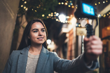 Fotomurales - Traveler female blogger shooting video for vlog social media with digital camera. Smiling woman vlogger taking photo selfie on background light night city illuminations