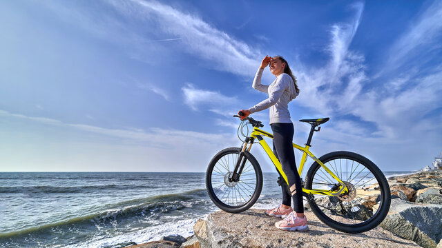 Fitness woman with a bicycle stands on the stones on the seashore and looks into the distance on a clear sunny day. Athletic healthy people with sporty and active lifestyle