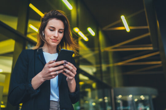 Successful female banker using smartphone outdoors while standing near his office background yellow neon lights, young woman professional manager working on mobile device near skyscraper at night
