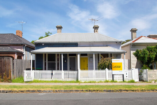 Williamstown, Australia: March 07, 2019: Traditionally built semi-detached bungalow with white picket fence. One house is rundown and requires repairs and the other is advertised for lease or rental.