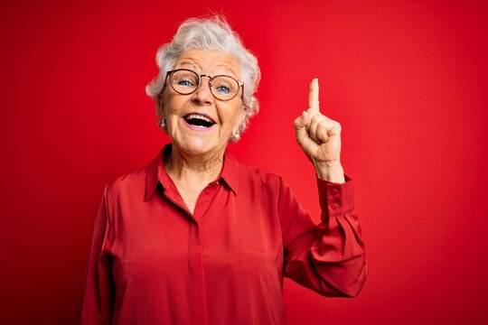 Senior beautiful grey-haired woman wearing casual shirt and glasses over red background pointing finger up with successful idea. Exited and happy. Number one.