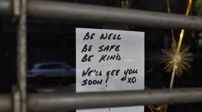 """Handwritten sign in a shop window reading """"Be well be safe be kind we'll see you soon! xo"""", behind a metal security gate barrier, May 31, 2020, in New York."""
