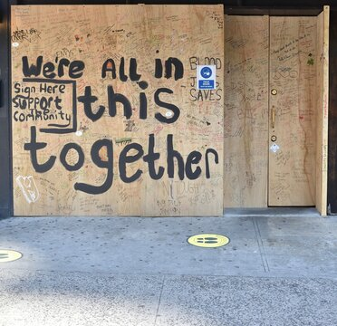"""""""We're all in this together. Sign here support the community"""" hand-painted on plywood filled with signatures, & social distancing footprint decals on the sidewalk, May 14, 2020, in New York."""