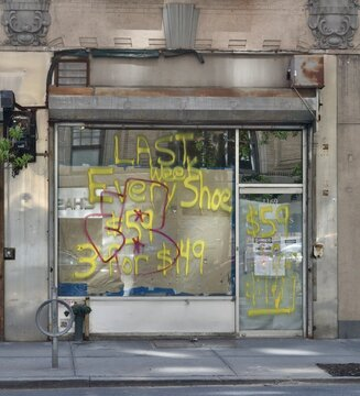"""Spray-painted message on a closed shopfront reading """"Last Week Every Shoe $59 3 For $149"""", with graffiti and brown paper taped to the inside of the front window and door, May 10, 2020, in New York."""