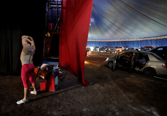 An acrobat stretches before presenting his act during a circus performance in Atayde's Circus tent, where people enjoy the show from their cars as a measure to combat the spread of the coronavirus disease (COVID-19), in San Nicolas de