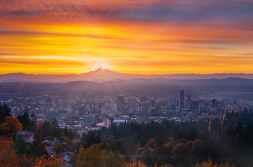 Portland downtown with  autumn foliage in thin fog, shining sunrise and colorful clouds