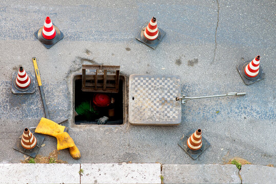 sequence of worker going in the manhole in the street, step 4