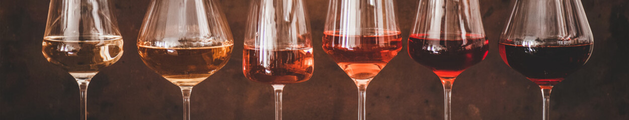 Various shades of Rose wine in stemmed glasses placed in line from light to dark colour on concrete table, rusty brown background behind, wide composition. Wine bar, wine shop, wine tasting concept Fotomurales
