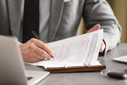 Male agent with car insurance form, closeup