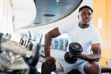 Young African American man sitting and lifting a dumbbell close to the rack at gym. Male weight...