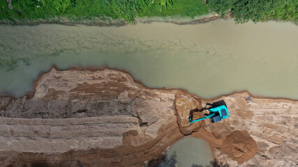 Environmental conservation issue. Machinery mining river, causing siltation and pollution