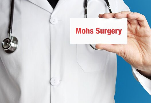 Mohs Surgery. Doctor in smock holds up business card. The term Mohs Surgery is in the sign. Symbol of disease, health, medicine