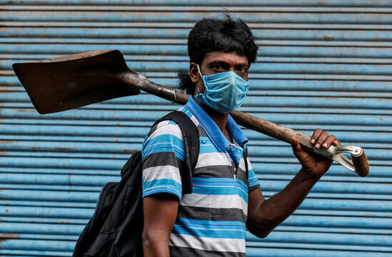 A migrant worker wearing a protective face mask goes to work after few restrictions were lifted, during an extended nationwide lockdown to slow the spread of the coronavirus disease (COVID-19), in Kochi