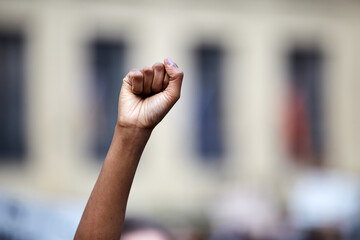 """Hand in fist at a """"black lives matter"""" rally in gathering, large group of protesters."""