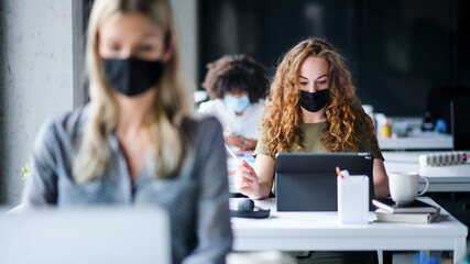 Aluminium Prints Equestrian Young people with face masks back at work or school in office after lockdown.