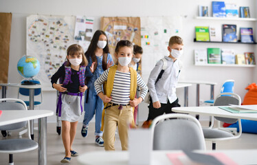 Group of children with face mask back at school after covid-19 quarantine and lockdown. - fototapety na wymiar