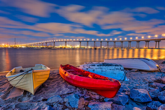 Colorful dinghy boats on a sandy beach along the bay with the San Diego–Coronado Bridge in the distance at night.