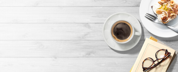 白木のテーブルの上に乗ったコーヒー、本、眼鏡、ケーキ。コーヒーブレイクもしくは読書のイメージ