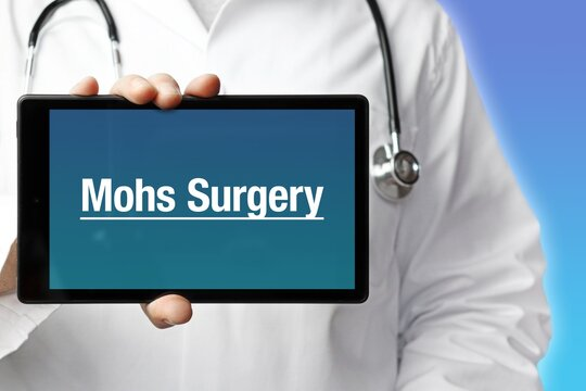 Mohs Surgery. Doctor in smock holds up a tablet computer. The term Mohs Surgery is in the display. Concept of disease, health, medicine