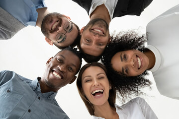 Portrait close up bottom view happy faces of diverse employees team standing in circle, looking at camera, smiling businesswomen and businessmen engaged in team building, posing for photo Fotobehang