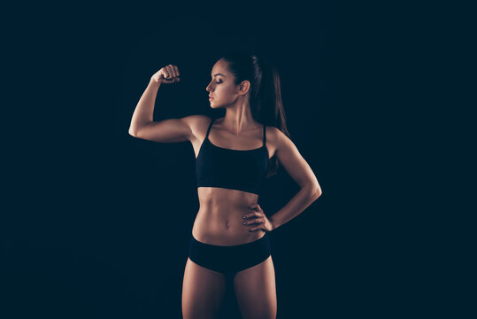 Portrait of her she nice-looking attractive content sportive perfect strong enduring lady fitness bikini model showing demonstrating powerful muscles isolated over black background