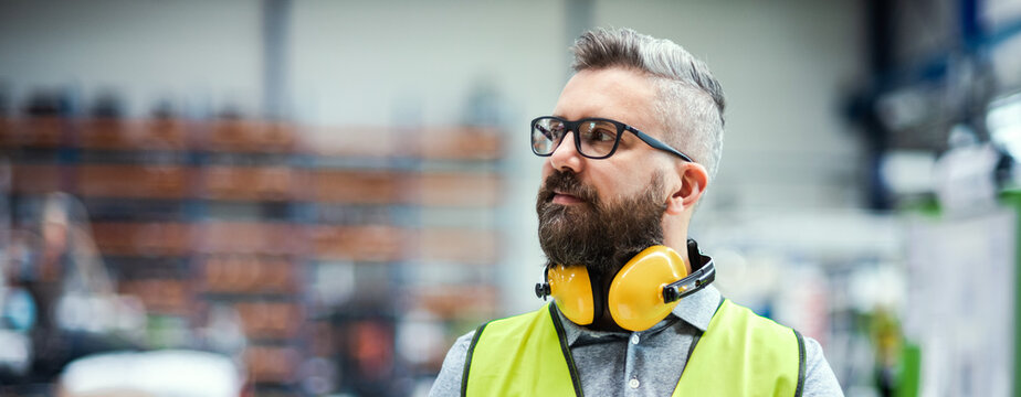 Technician or engineer with protective headphones standing in industrial factory.
