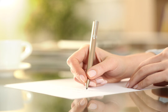 Woman hand writing on a paper on a desk at home