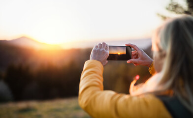 Senior woman hiker standing outdoors in nature at sunset, taking photograph.