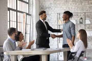 Smiling executive congratulating successful African American employee with promotion, shaking hands at corporate meeting, confident team leader greeting new member at briefing in boardroom